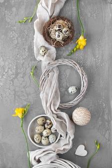 Пасхальная кладка с перепелиными яйцами в птичьем гнезде, льняной ткани и вокруг. желтые цветы фрезии и венок из ротанга на текстурированной доске. натуральные пасхальные украшения.