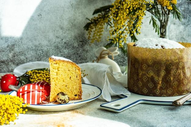 伝統的なケーキと春の花で飾られた色の卵とイースターフードのコンセプト