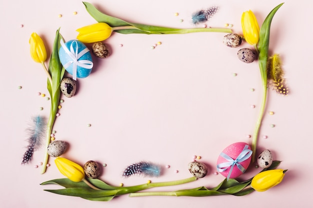 Easter frame of beautiful yellow tulips, decorated eggs and beads. holiday mock up