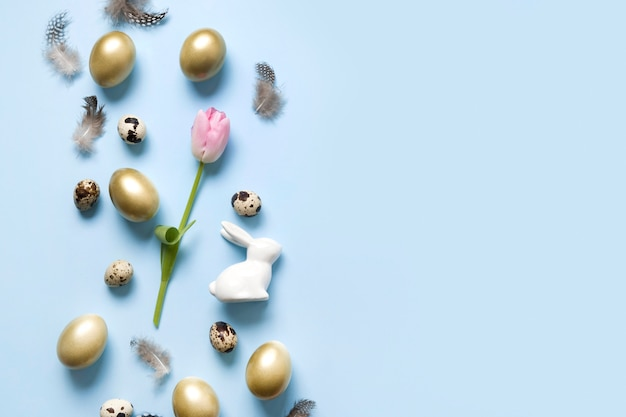 Easter frame of bunny, golden eggs, pink tulip on blue. top view. happy holiday.