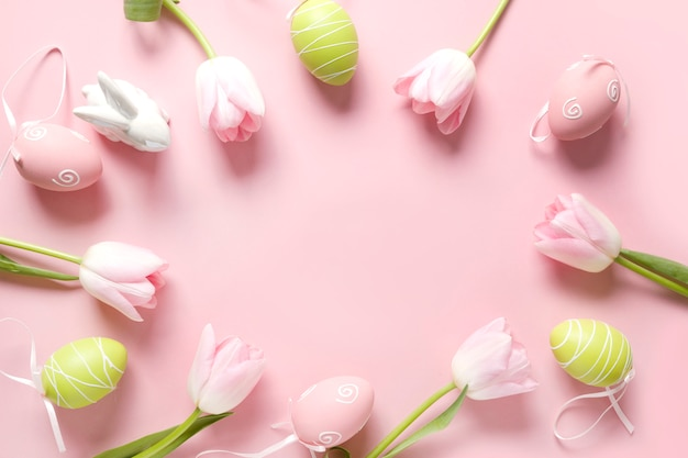 Easter frame of fresh pink flowers, colorful eggs and bunny on pink. top view, copy space. happy easter holiday.