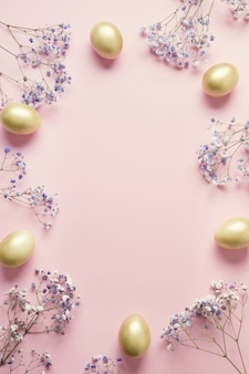 Easter frame of golden egg purple flowers on pastel pink. top view with copy space.