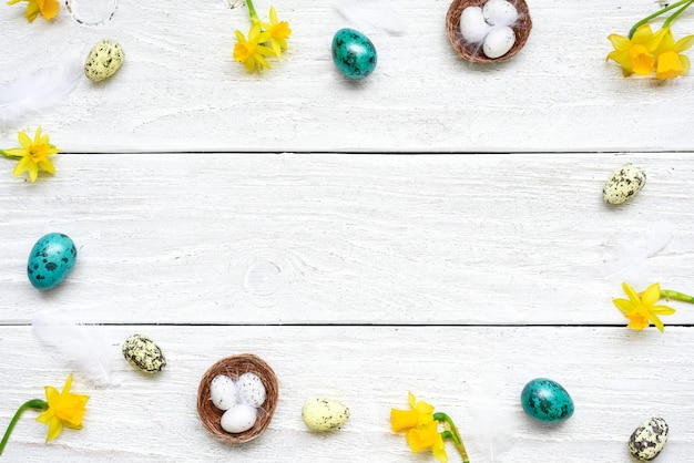 Easter frame made of eggs and spring flowers on white wooden table. easter composition