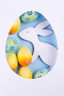 Easter frame made of paper, colorful painted chicken eggs, white wooden bunny on blue background. easter composition. flat lay,
