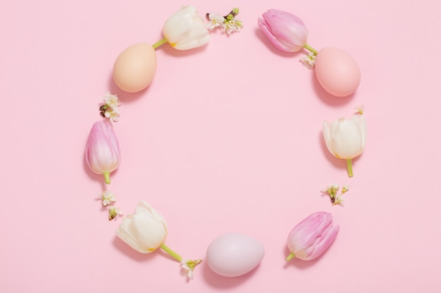 Пасхальная рамка из тюльпанов и крашенных яиц на розовом фоне