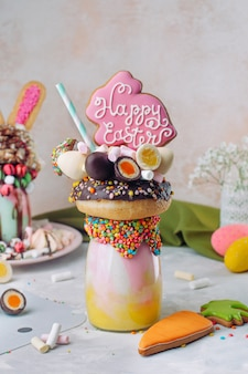 Easter freak shake decorated with easter bunny gingerbread on table