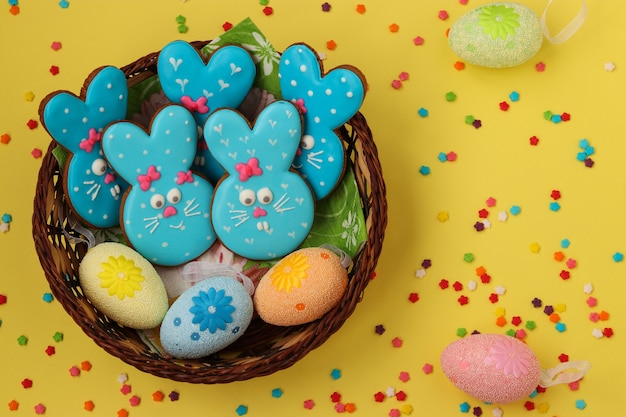 Easter funny blue rabbits, homemade painted gingerbread biscuits in glaze in a wicker basket on a yellow surface, top view