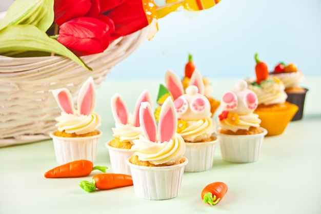 Easter funny bunny cupcake. easter celebration festive table. basket of flowers tulips on the background.