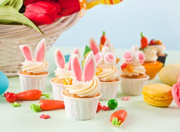 イースター面白いバニーカップケーキ。イースターのお祝いのお祝いのテーブル。背景に花のチューリップのバスケット。
