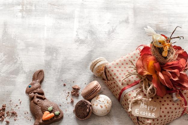 木製の背景にイースターギフトとお菓子。