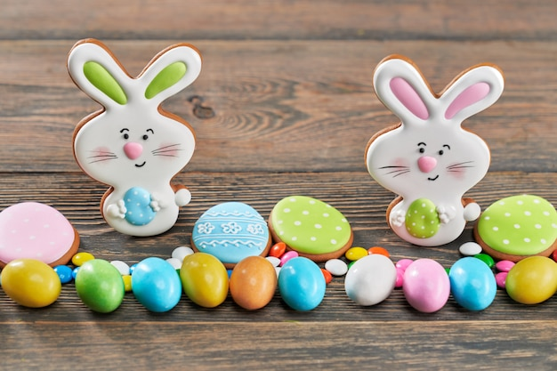 Easter ginger cookies and candies on wooden table.