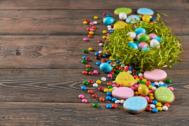 Easter ginger cookies and colorful eggs in nest.