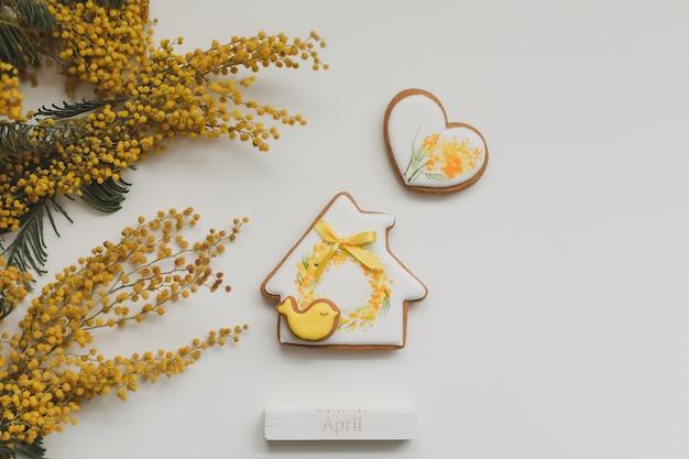 白い背景の上のイースタージンジャーブレッドクッキーとミモザの花。春、春、4月、ハッピーイースターのコンセプト。上面図