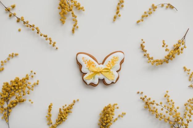 Пасхальные пряники и цветы желтой мимозы на белом