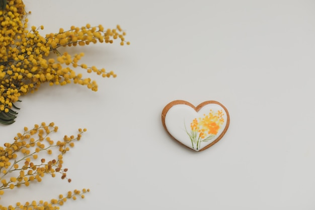 Easter gingerbread cookie in a shape of a heart and mimosa flowers on white background. top view copy space.