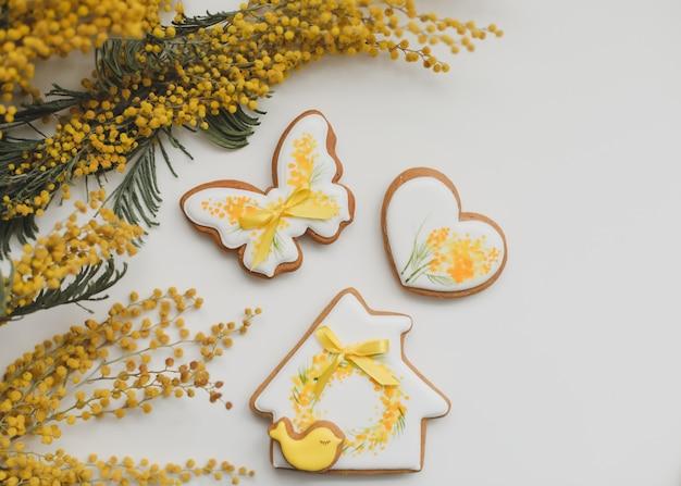 白い背景の上のイースタージンジャーブレッドクッキーとミモザの花。上面図のコピースペース。ハッピーイースターのコンセプト。