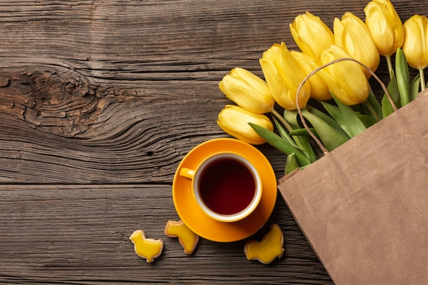 Easter gingerbread cookies, cup of tea on wooden table and yellow tulips. greeting card. top view with copy space.