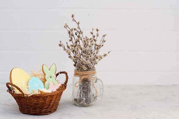 Easter gingerbread cookies and eggs in a vase with willow branches. egg shaped cookies.