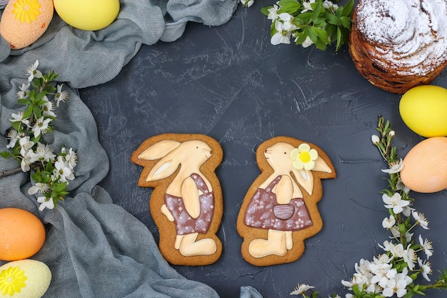 Easter gingerbread in the form of cute rabbits are located on a dark background