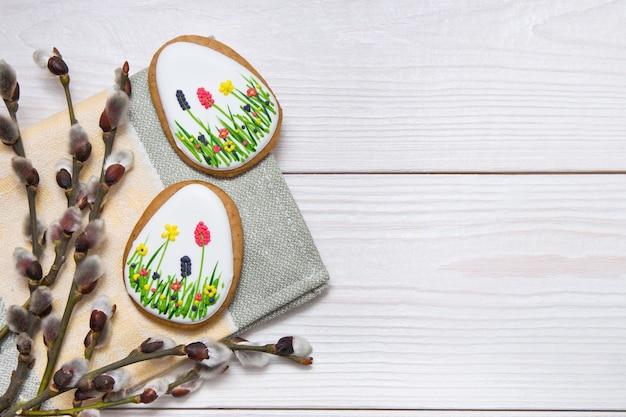 Набор пасхальных пряников и веточка ивы на белом деревянном