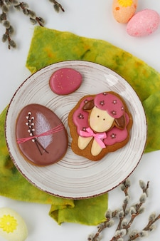 Easter gingerbreads in the form of cute sheep and eggs in a plate on white background, top view, the concept of the spring church holiday