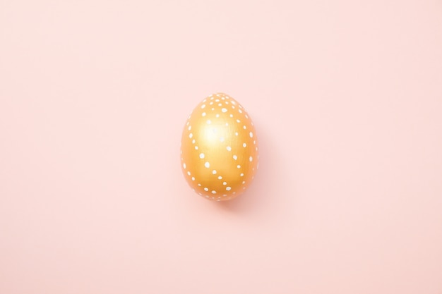 Easter golden decorated egg on pastel pink background. happy easter card