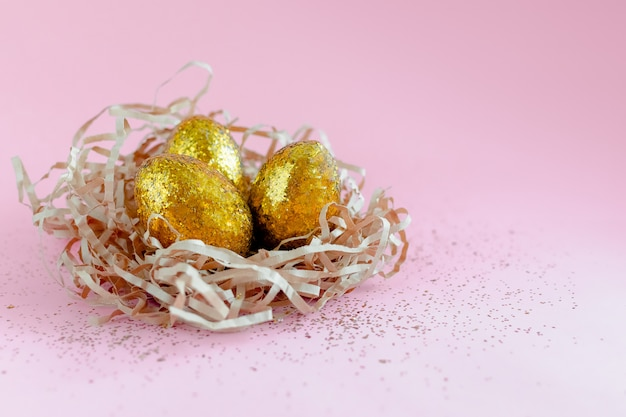 Easter golden decorated eggs in nest on pink background . minimal easter concept copy space for text.