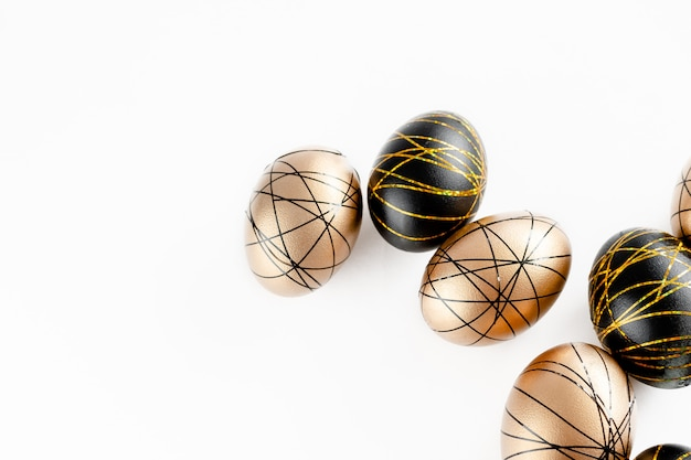 Easter golden decorated eggs in nest on white background . minimal easter concept copy space for text. top horizontal view, flatlay.