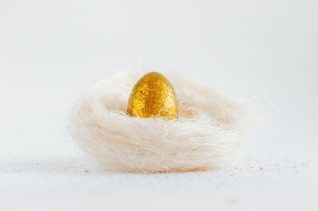 Easter golden decorated eggs in nest on white background . minimal easter concept copy space for text.