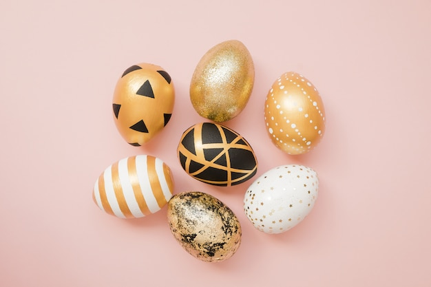 Easter golden decorated eggs on pastel pink background