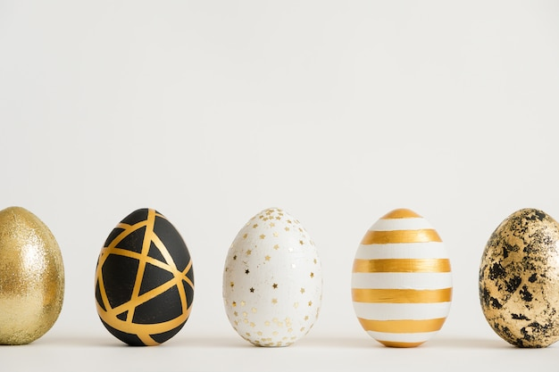 Easter golden decorated eggs stand in a row