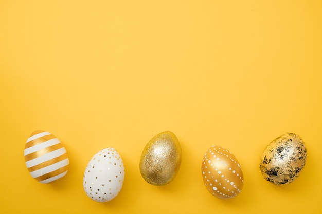 Easter golden decorated eggs on yellow background. happy easter card