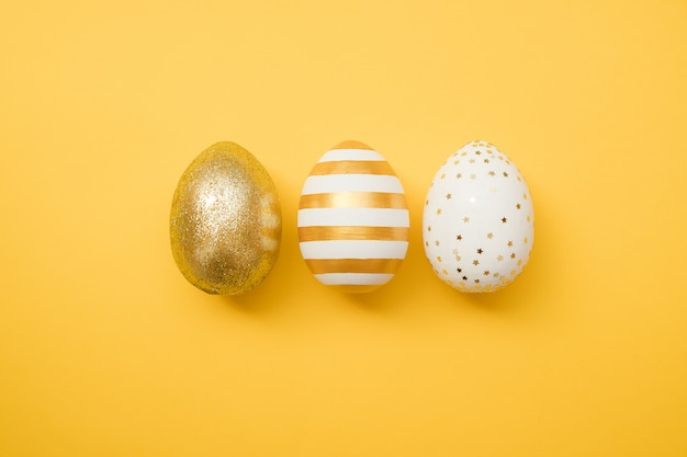 Easter golden decorated eggs on yellow background. minimal easter