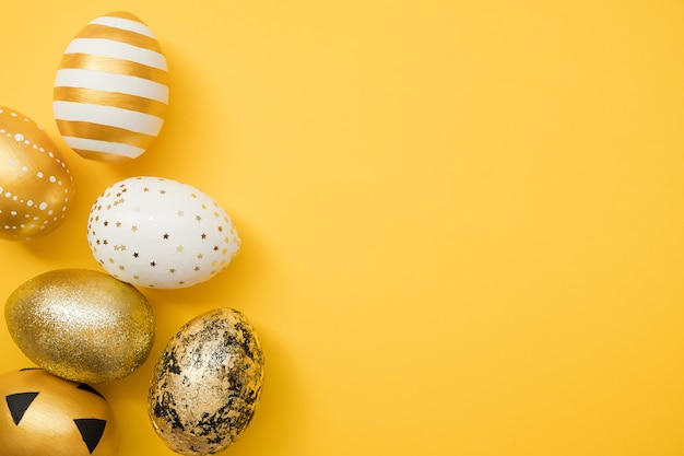 Easter golden decorated eggs on yellow background