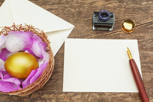 手紙を書くペンの近くの黄金のイースターエッグ。