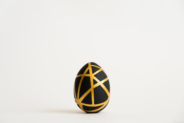 Easter golden egg with geometric black pattern isolated on white background