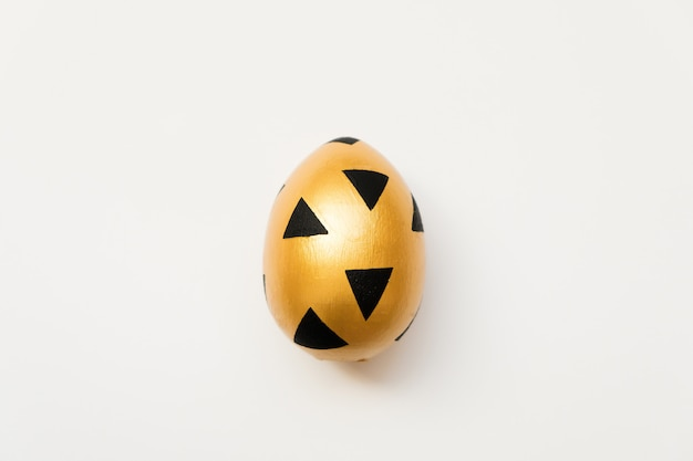 Easter golden egg with triangular black pattern isolated on white background
