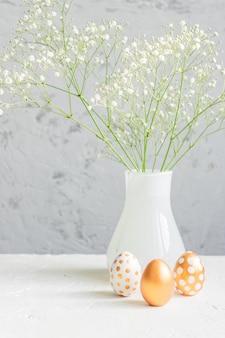黄金のイースターエッグと灰色の壁の背景にカスミソウの花の花束。休日のためのお祝いの居心地の良い静物。インテリア。