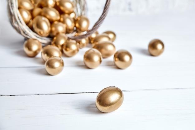 白い木製のテーブルの枝編み細工品バスケットから黄金のイースターエッグがこぼれた。セレクティブフォーカス