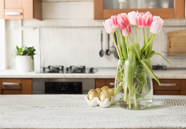Easter golden painted eggs and spring bouquet in kitchen. indoors.