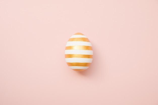パステルピンクの背景に縞模様の卵と黄金のイースター
