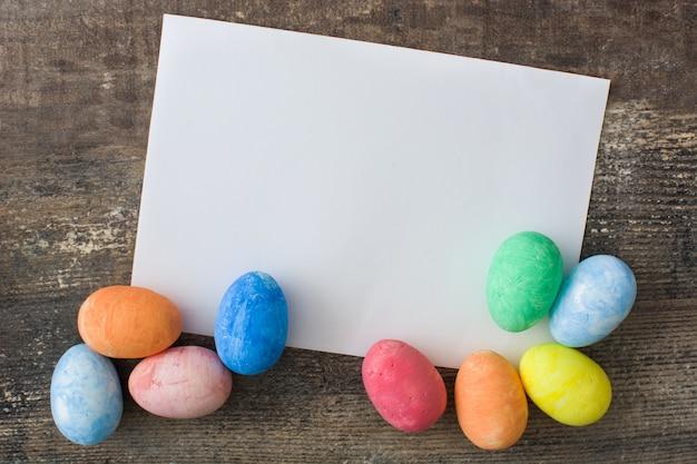 Пасхальная открытка и пасхальные яйца на деревянный стол
