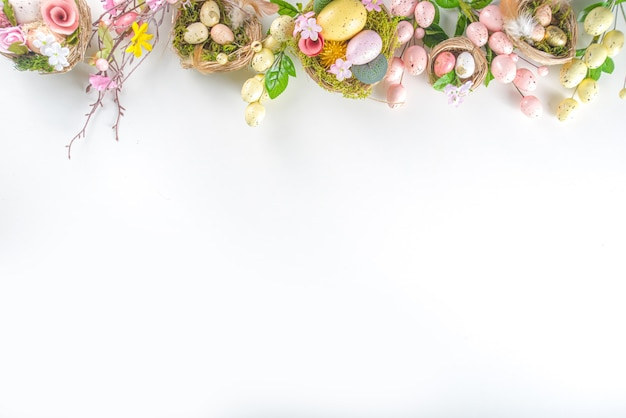 Easter greeting card background. spring tree decor branches with colorful eggs, flowers and leaves on white background copy space for your text