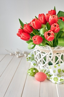 Easter greeting card design with bunch of red tulips on light