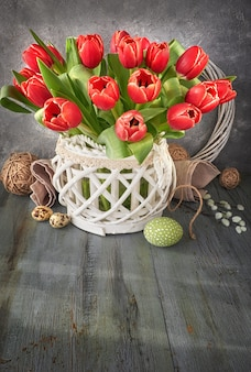Easter greeting card design with bunch of red tulips on rustic wall with easter decorations, text space