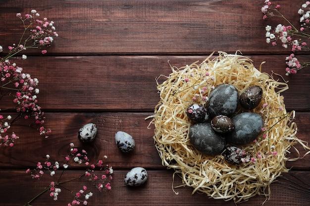 イースターグリーティングカードコピースペースのある暗い木製のテーブルに自然に染められた卵と花の装飾が施された巣