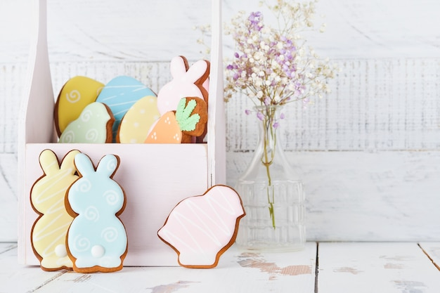 Пасхальная открытка с красочными красочными кроликами, яйцами, цыплятами и морковью имбирные пряники корзина перед деревянной стеной. вид сверху.