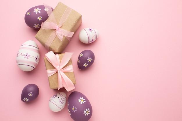 Поздравительная открытка пасхи с красочными пасхальными яйцами и подарком на розовом фоне.