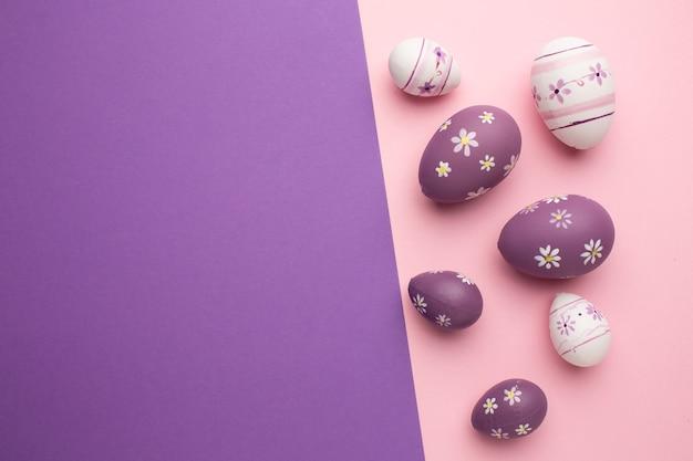 Поздравительная открытка пасхи с красочными пасхальными яйцами на розовых и фиолетовых предпосылках.