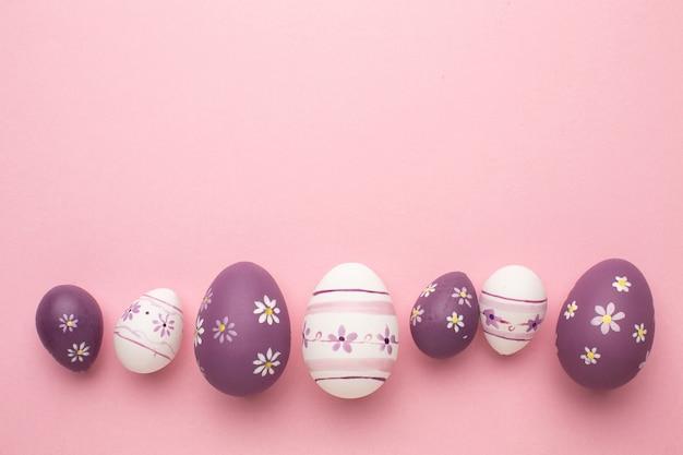 Поздравительная открытка пасхи с красочными пасхальными яйцами на розовом фоне.